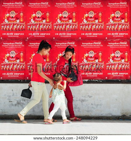 Tuaran Sabah Malaysia - January 29, 2015 : Unidentified people pass by Coca-Cola poster for Chinese New Year 2015 festival at Pekan Tuaran. Lunar New Year of the Goat will fall on February 19,2015. - stock photo