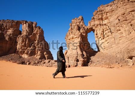 Tuareg and stone arch in the Sahara Desert - stock photo