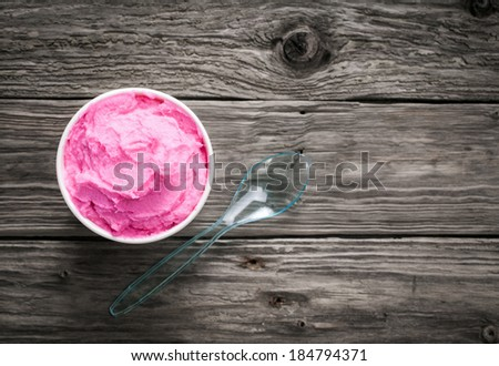 Tub of colorful pink Italian berry ice cream on a rustic wood table in a plastic takeaway tub with a teaspoon and copyspace - stock photo