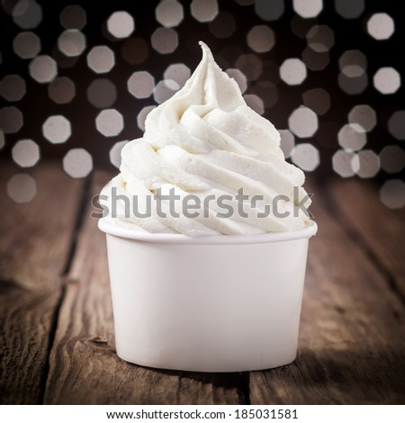 Tub of creamy vanilla or tangy lemon ice cream on an old wooden bar counter with a bokeh of festive party lights - stock photo