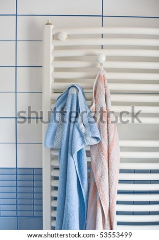 tube radiator in bathroom with blue and white wall and towels pending casual - stock photo