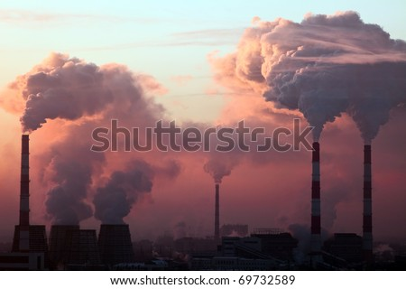 Tube with orange smoke on winter sunset - stock photo