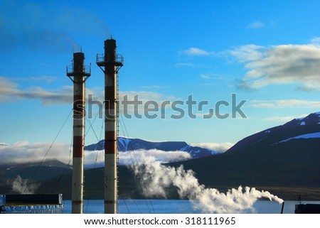 Tubes and smoke from Combined heat and power station against the background of black rocks, blue sky and water of Istfjorden in Barentsburg, Spitsbergen (Svalbard island), Norway, Greenland Sea - stock photo