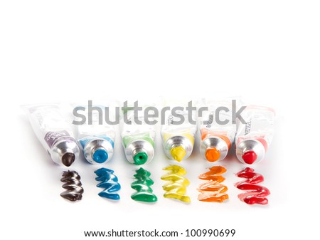 Tubes of rainbow colored paint on white background - stock photo