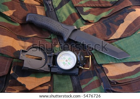 Tubular compass, and blackened knife laying on a camoflaged vest - stock photo