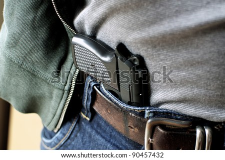 Tucked in a belt pistol being concealed - stock photo