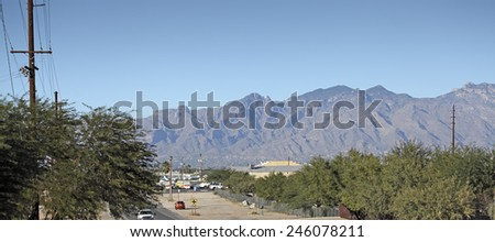 TUCSON, AZ - NOVEMBER 25, 2014: Mixed residential and business streets of South Tucson with a backdrop of Santa Catalina mountain range and blue sky - stock photo