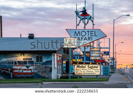 TUCUMCARI, NEW MEXICO - SEPT 6, 2014: Motel Safari, a Route 66 icon, at sunset with neon signs and mural of Trailways tour bus with Tucumcari Tonite as its destination. - stock photo