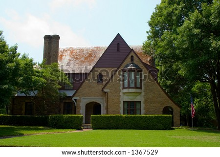 Tudor Style brick house with dramatically pitched roofline - stock photo