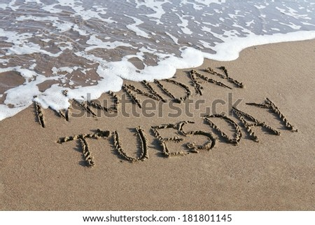 Tuesday is coming concept - inscription Monday and Tuesday written on a sandy beach, the wave is starting to cover the word Monday. - stock photo