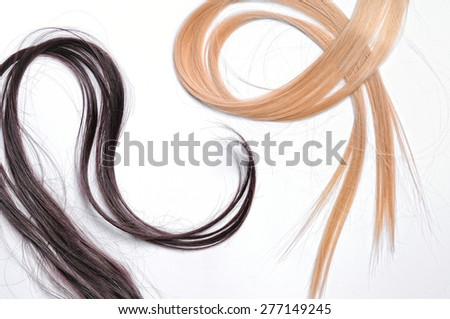 Tufts of brown and blond straight hair with isolated white background - stock photo