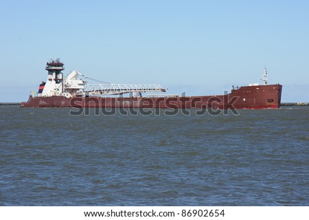 Tug and Barge:  A bulk carrier cargo vessel comprised of a self-unloading barge with a tug boat for power enters the Port of Cleveland, Ohio from Lake Erie - stock photo