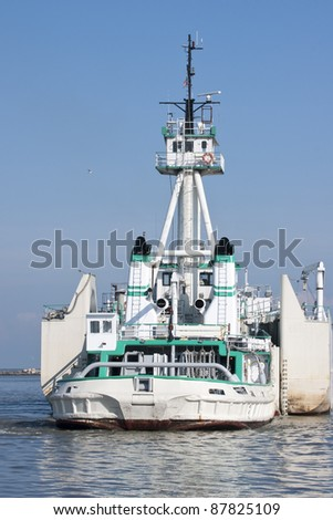 Tug and Barge:  A large twin engine tugboat is matched with a barge in an articulated fashion, allowing for cost effective transportation of cement across the Great Lakes - stock photo