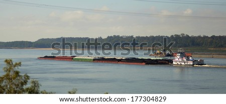 Tug boat and barges of petroleum oil passes under the Vicksburg Bridge along the Mississippi River - stock photo