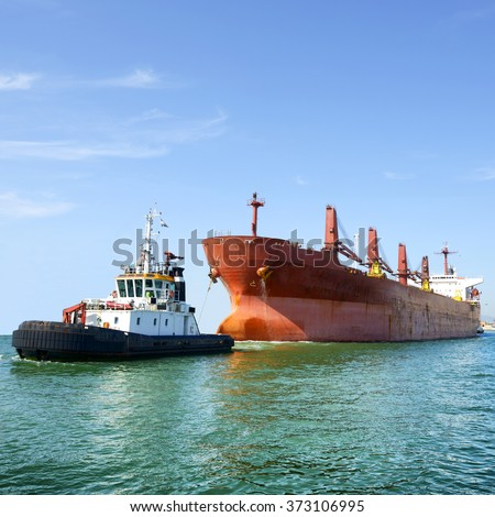 Tug boat and cargo ship entering the harbor - stock photo