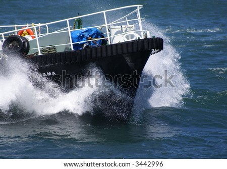 Tug boat bow creating spray - stock photo