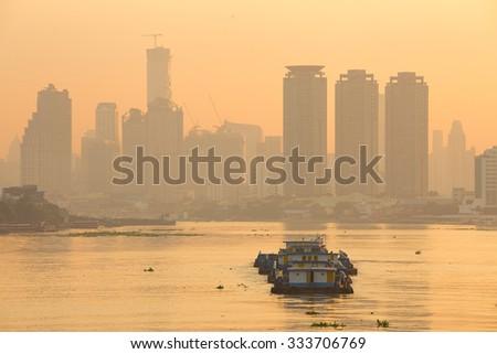 Tug boat drags sand barge on Chao Phraya river, Bangkok - stock photo