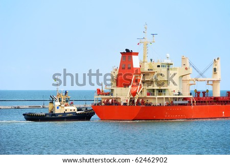 Tug boat helps to maneuver the ship in port
