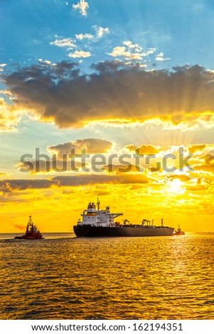 Tug boat pulling the tanker ship at sea. - stock photo