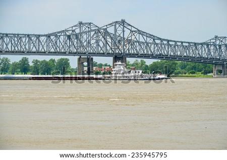 Tug boat pushing loaded barges beneath the Mississippi River Bridge between Natchez Mississippi and Louisiana. - stock photo
