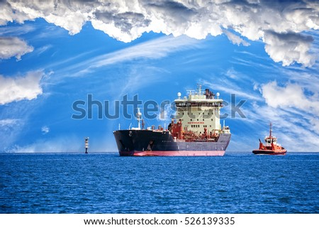Tug boat towing a tanker ship at sea.