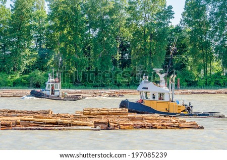 Tug boats work with log boom. - stock photo