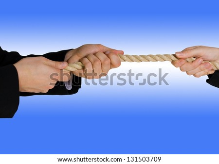 tug of war between business people with blue background - stock photo