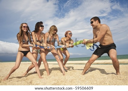 Tug-of-war between girls and guy on the beach - stock photo