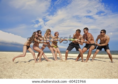 Tug-of-war between girls and guys on the beach - stock photo