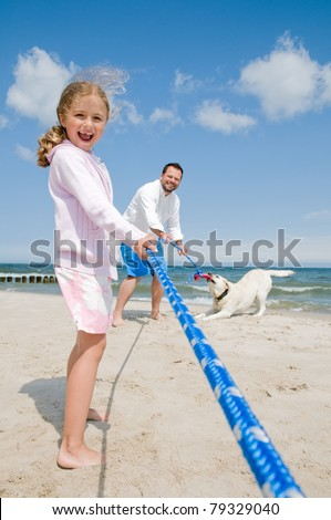 Tug of war - family with dog playing on the beach