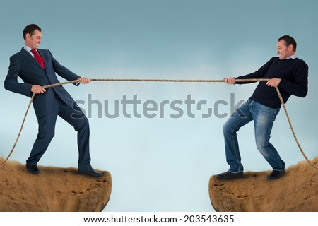 tug of war men pulling rope over a crevasse  - stock photo