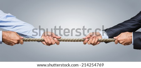 Tug war, two businessman pulling a rope in opposite directions isolated on gray background - stock photo