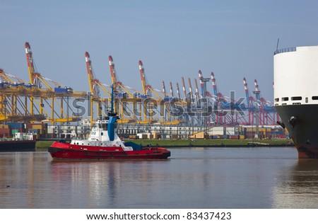 tug with heavy ship in the harbor - stock photo