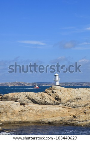 Tugboat and lighthouse at sea archipelago - stock photo