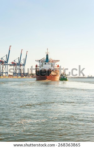 Tugboat assisting bulk cargo ship in a harbor of Klaipeda. Lithuania.  Front view. Outdoors image.