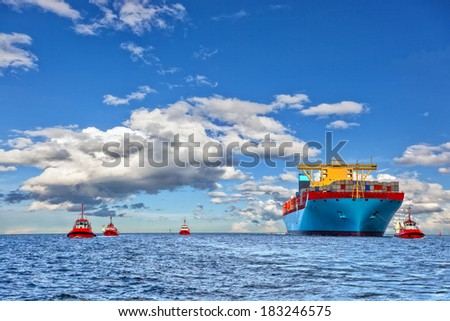Tugboat assisting container cargo ship to harbor. - stock photo