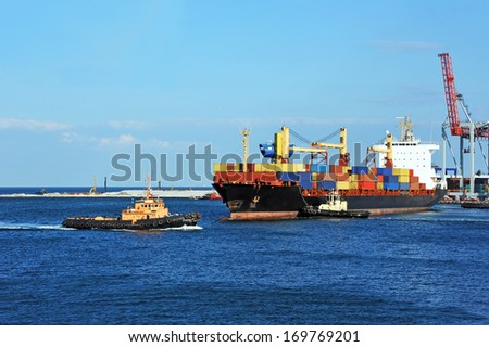 Tugboat assisting container cargo ship to harbor quayside - stock photo