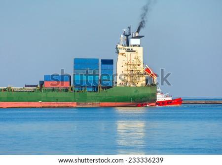 tugboat assisting huge vessel  - stock photo