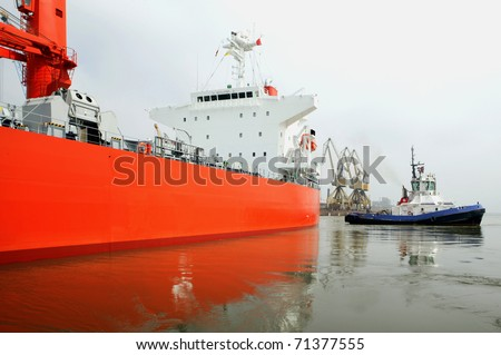 Tugboat at work. Oil and gas supertanker - stock photo