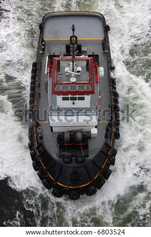 Tugboat in the Caribbean following cruise ship - see more in portfolio - stock photo