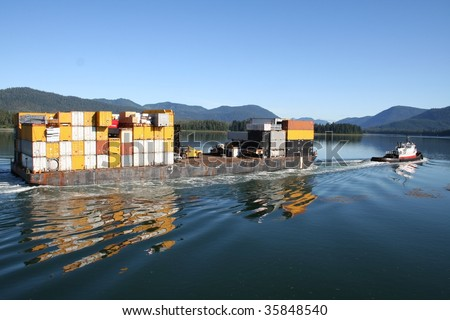 Tugboat towing a barge full of shipping containers through the Wrangell Narrows in Southeastern Alaska
