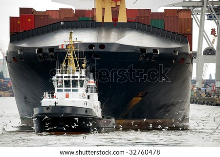 tugboat towing container ship freighter in harbor - stock photo