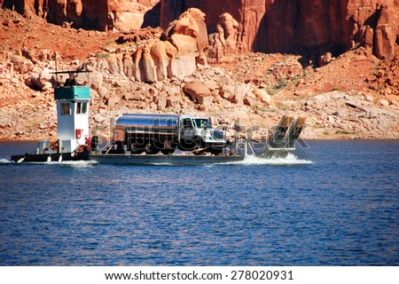 Tugboat transports barge loaded with a tanker truck on Lake Powell in Arizona. - stock photo