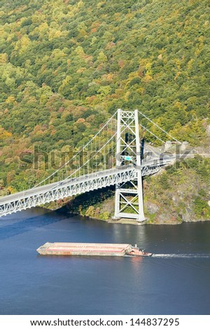 Tugboat with barge under Bear Mountain Bridge and Hudson Valley and River at Bear Mountain State Park, New York - stock photo