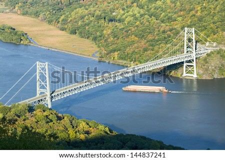 Tugboat with barge under Bear Mountain Bridge and Hudson Valley at Bear Mountain State Park, New York - stock photo