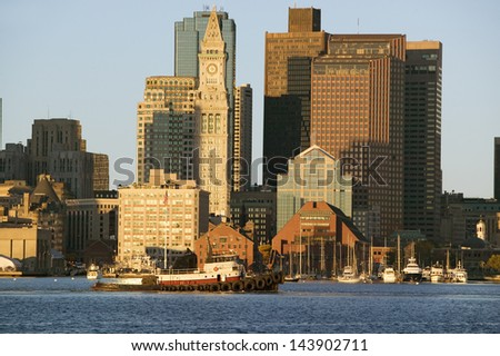 Tugboat with Boston Harbor and the Boston skyline at sunrise as seen from South Boston, Massachusetts, New England - stock photo