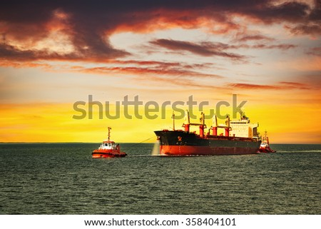Tugboats assisting cargo ship on sea in the morning. - stock photo