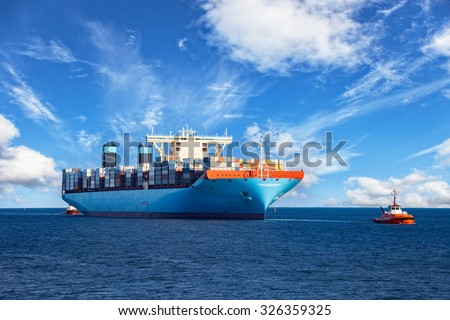 Tugboats assisting container cargo ship to harbor. - stock photo