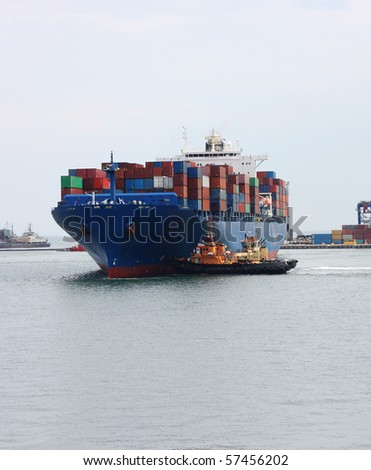tugboats pulling a container vessel - stock photo