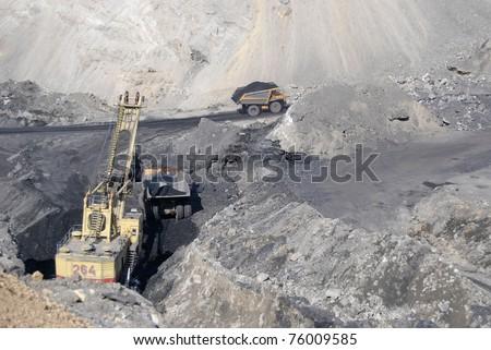 TUGNUI, RUSSIA - APRIL 2:  A mining shovel puts coal into a hauler at the opening of Tugnuiskaya coal-preparation plant on April, 2, 2008 in Tugnui, Buryatia, Russia. - stock photo